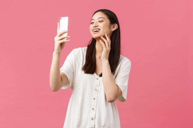 Schoonheid, mensenemoties en technologieconcept. vrouwelijke knappe stijlvolle aziatische vrouw blogger selfie te nemen op smartphone camera, glimlachend gelukkig op mobiele telefoon, roze muur staan