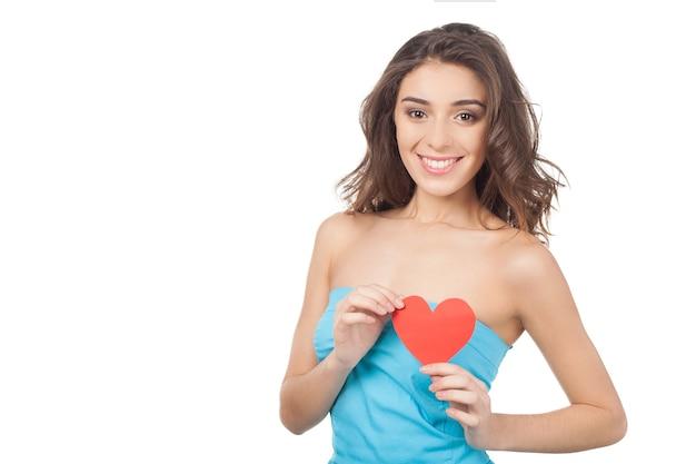 Schoonheid met papieren hart. mooie jonge vrouw die een rood papieren hart vasthoudt en naar de camera glimlacht terwijl ze op een witte achtergrond staat