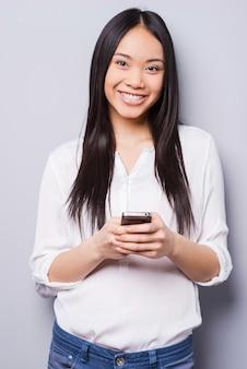 Schoonheid met telefoon. vrolijke jonge aziatische vrouw die mobiele telefoon vasthoudt en glimlacht terwijl ze tegen een grijze achtergrond staat
