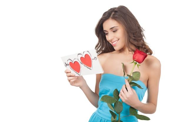 Schoonheid met valentijnskaart. mooie jonge vrouw die een rode roos vasthoudt en een valentijnskaart leest terwijl ze op een witte achtergrond staat