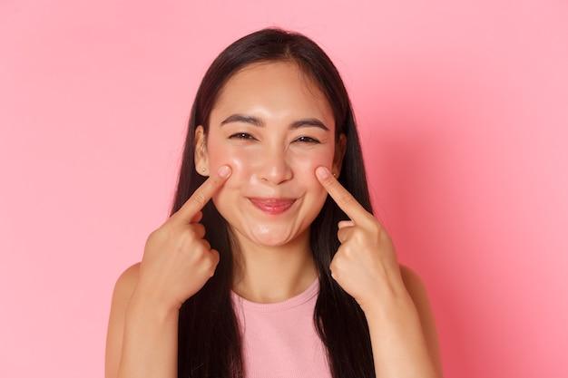 Schoonheid mode en lifestyle concept close-up van dom en schattig schattig aziatisch meisje haar wangen porren...