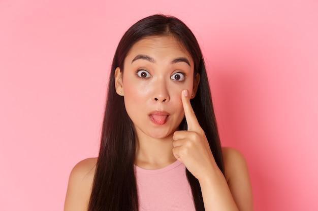 Schoonheid mode en lifestyle concept close-up van domme en grappige schattig aziatisch meisje ooglid trekken en s...