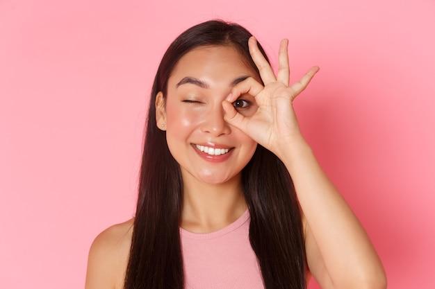Schoonheid, mode en lifestyle concept. portret van kawaii aantrekkelijk aziatisch meisje dat ok gebaar over oog toont en zorgeloos knipoogt, tevreden glimlacht, waarborg kwaliteit, plaats raadt.