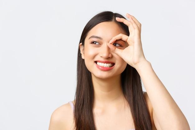 Schoonheid, mode en mensen emoties concept. dromerig mooi aziatisch meisje met een gelukkige glimlach, die de linkerbovenhoek met ok teken over oog kijkt