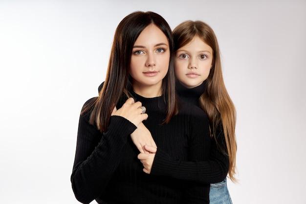 Schoonheid mode portret moeder en dochter in een zwarte coltrui en blauwe denim rok. vrouw en meisje, familie