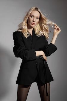 Schoonheid mode sexy vrouw in een jas en panty's, een blond meisje met lange benen. perfecte figuur van een model, portret van een vrouw op een grijze achtergrond