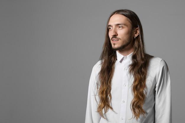Schoonheid, mode, stijl en mensenconcept. geïsoleerde shot van buitengewone modieuze jonge man met lange losse haren, baard en oorbel die zich voordeed op grijze muur, stijlvol wit overhemd dragen, glimlachend