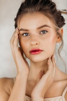 Schoonheid model gezonde huid hand manicure nagels aanraken van schone huid vrouwen cosmetica mooi fris schoon vrouwelijk gezicht.