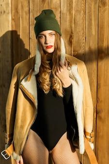 Schoonheid model meisje in een bruine jas lamsvacht poseren in de studio. mooie luxe winter vrouw.