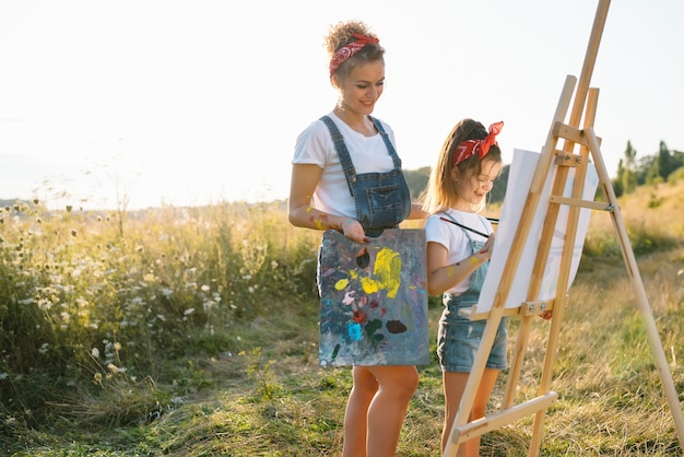 Schoonheid moeder schildert met haar dochtertje. stijlvolle vrouw die de afbeelding met een klein meisje tekent. schattige jongen in een wit t-shirt en spijkerbroek.