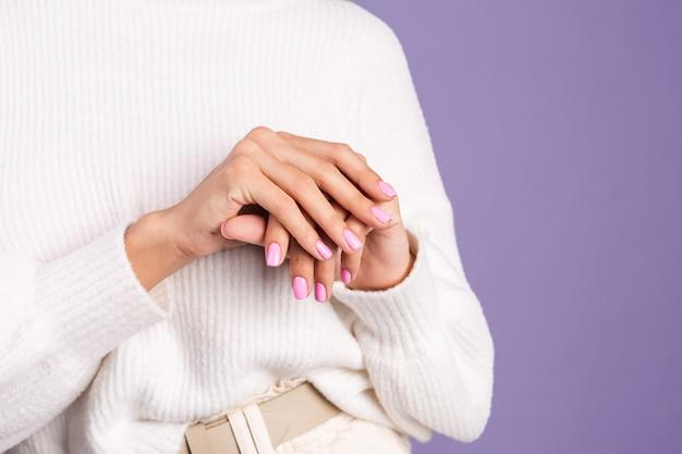 Schoonheid nagel concept, kleine roze lente kleur manicure witte trui paarse muur