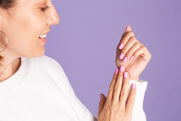 Schoonheid nagel concept, kleine vrouw met roze lente kleur manicure witte trui paarse muur