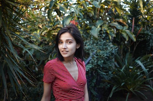 Schoonheid, natuur en jeugdconcept. prachtige jonge donkerharige vrouw met bob kapsel met mooie wandeling in het park, genietend van ochtendzon en frisheid afkomstig van groene verse planten om haar heen