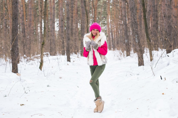 Schoonheid, natuur en mensen concept - mooie blonde vrouw wandelen in roze hoed en truien in de winter