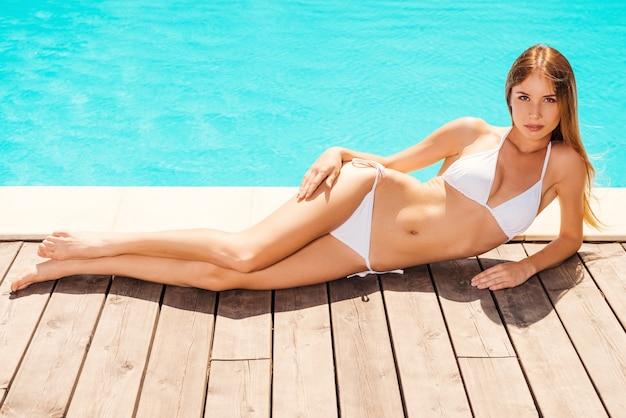 Schoonheid ontspannend aan het zwembad. volledige lengte van mooie jonge vrouw in witte bikini die bij het zwembad ligt en glimlacht