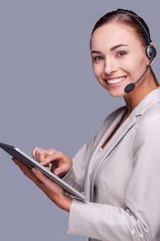 Schoonheid op het werk. zijaanzicht van zelfverzekerde jonge vrouwelijke operator met digitale tablet