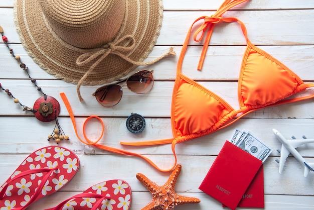 Schoonheid oranje bikini en accessoires op houten vloer voor reis op zomer