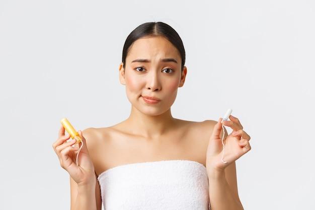 Schoonheid, persoonlijke en intieme zorg menstruele hygiëne concept. schattig besluiteloos aziatisch meisje op haar perion staat in een handdoek en houdt tampons vast met en zonder applicator, weet niet wat je moet kiezen.