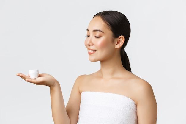 Schoonheid, persoonlijke verzorging, kuuroordsalon en huidverzorgingsconcept. close-up van mooie aziatische vrouw in badhanddoek introduceren gezichtscrème, hydraterende of hydraterende behandeling voor gezicht, voedende huid.