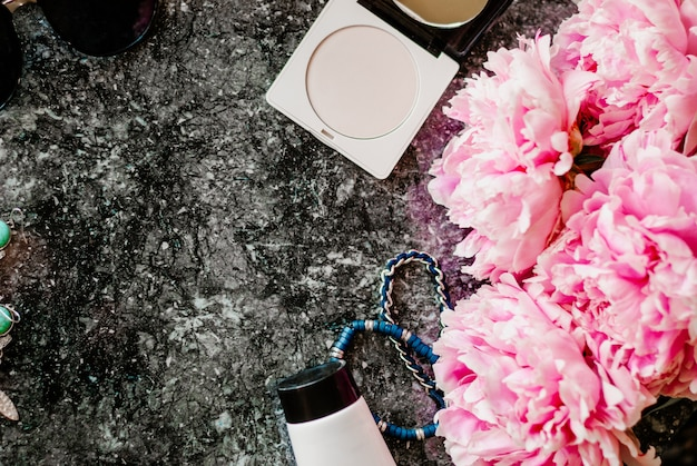 Schoonheid plat lag met accessoires, parfum, cosmetica en pioenrozen op een donkere marmeren achtergrond