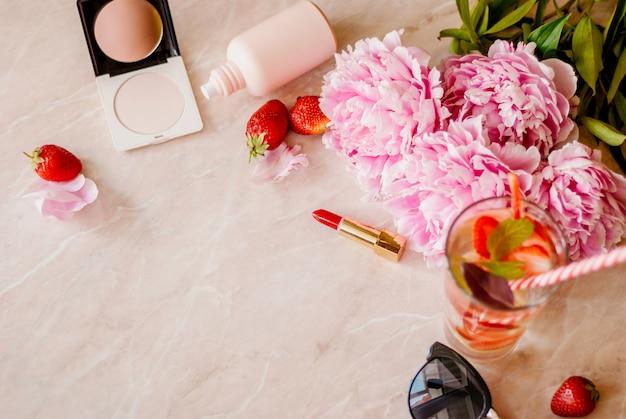 Schoonheid plat lag met een cosmetica, parfum, detox water met aardbei en pioenrozen op een marmeren achtergrond