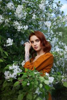Schoonheid portret roodharige vrouw in het voorjaar in de takken van een appelboom