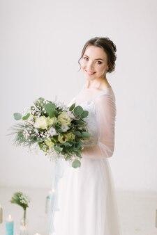 Schoonheid portret van bruid poseren in de studio voor de huwelijksceremonie in mode trouwjurk met luxe verrukking make-up en kapsel