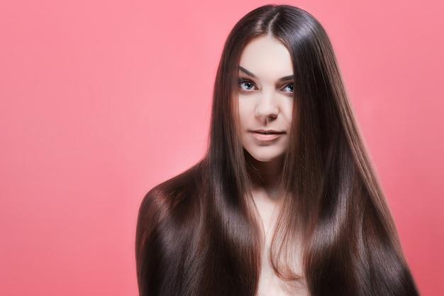 Schoonheid portret van brunette met perfect haar, op een roze muur. haarverzorging