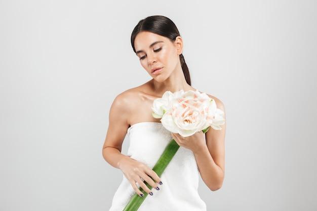 Schoonheid portret van een aantrekkelijke sensuele gezonde vrouw geïsoleerd over witte muur, poseren met een bloem