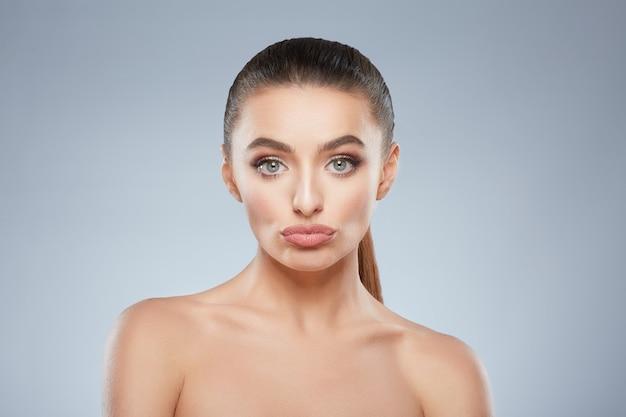 Schoonheid portret van een beetje verdrietig meisje kijken camera ellendig. hoofd en schouders van mooie vrouw medelijden. natuurlijke make-up, studio, echte emoties