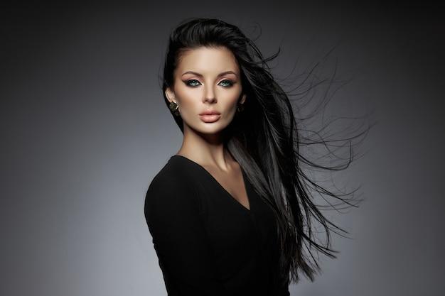 Schoonheid portret van een brunette vrouw met haar in de wind vliegen. professionele make-up, perfect gezicht van een sexy vrouw