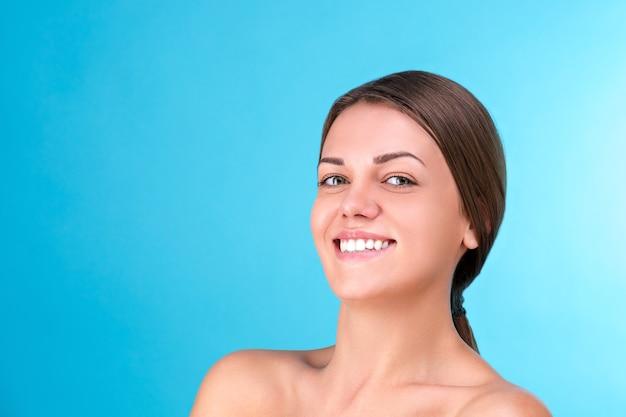 Schoonheid portret van een jonge aantrekkelijke half naakte vrouw met perfecte huid lachen en kijken naar camera geïsoleerd over blauw oppervlak