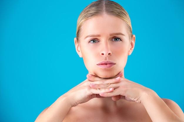 Schoonheid portret van een jonge vrouw haar gezicht aan te raken