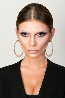Schoonheid portret van een jonge vrouw, het dragen van metalen ronde oorbellen, catwalk schoonheid look
