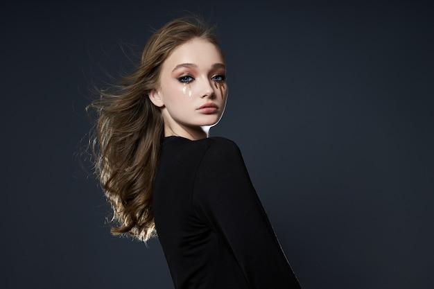 Schoonheid portret van een meisje met creatieve make-up, een vrouw huilen met mascara gemaakt van pailletten