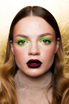 Schoonheid portret van een meisje met sproeten en een creatieve make-up. bordeauxrode matte lippenstift op de lippen.