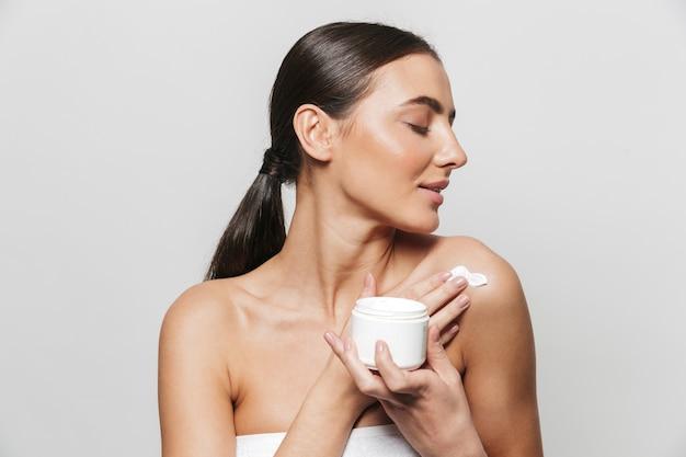 Schoonheid portret van een mooie jonge vrouw gewikkeld in een handdoek staande geïsoleerd, lichaam crème uit een container toe te passen