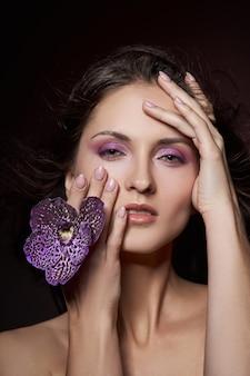 Schoonheid portret van een naakte vrouw met een paarse bloem in haar handen op een donkere achtergrond. natuurlijke cosmetica, natuurlijke make-up