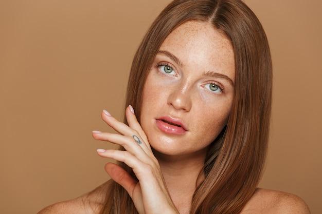 Schoonheid portret van een sensuele jonge topless vrouw met lang rood haar poseren, hand in hand op haar gezicht geïsoleerd over beige muur