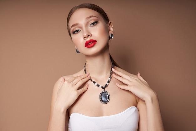 Schoonheid portret van een vrouw met sieraden, oorbellen in haar oren en een ketting om haar nek. perfect schone gezichtshuid, natuurlijke cosmetica