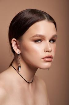 Schoonheid portret van een vrouw met sieraden, oorbellen in haar oren en een ketting om haar nek