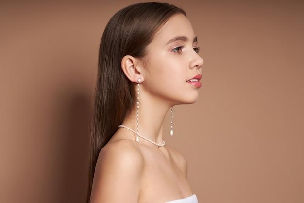 Schoonheid portret van een vrouw met sieraden, oorbellen in haar oren en een ketting om haar nek.