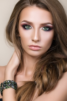 Schoonheid portret van jong mooi meisje met groene ogen dragen groene armband en haar haar aan te raken