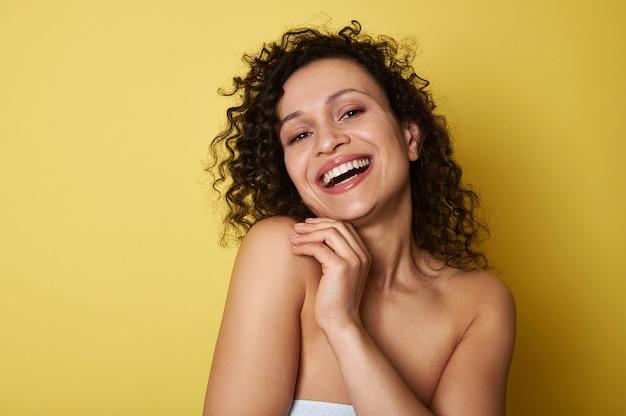 Schoonheid portret van jonge half naakte vrouw met krullend haar glimlachend brede glimlach camera kijken, poseren over geel allemaal met kopie ruimte