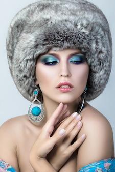 Schoonheid portret van jonge mooie dame bont glb en blauwe oorbellen dragen. wintermode make-up