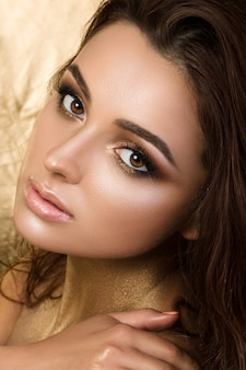 Schoonheid portret van jonge mooie vrouw met fashion make-up. gebronsde huid en gouden smokey eyes.