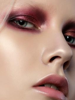 Schoonheid portret van jonge vrouw met perfecte huid en rode smokey eyes.