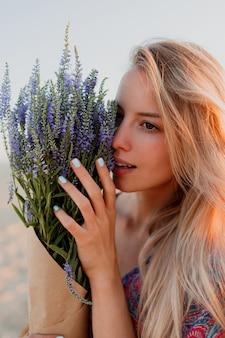 Schoonheid portret van mooie blonde vrouw met boeket van lavendel camera kijken. perfecte huid. natuurlijke make-up.