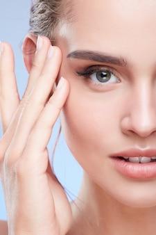 Schoonheid portret van mooie vrouw tempels aan te raken. half gezicht van vrouw met naakte make-up, schoonheidsconcept, close-up.