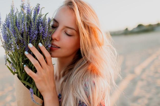 Schoonheid portret van romantische blonde vrouw met boeket van lavendel camera kijken. perfecte huid. natuurlijke make-up.